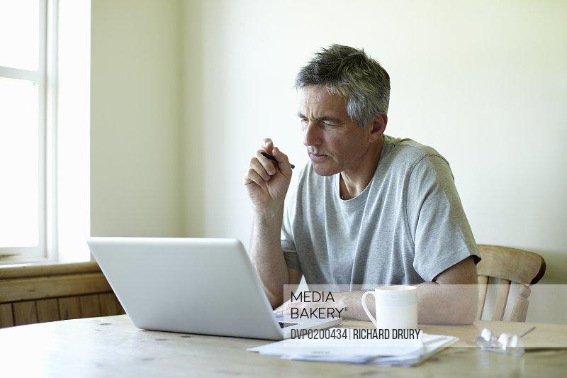 Man sitting at kitchen table using laptop