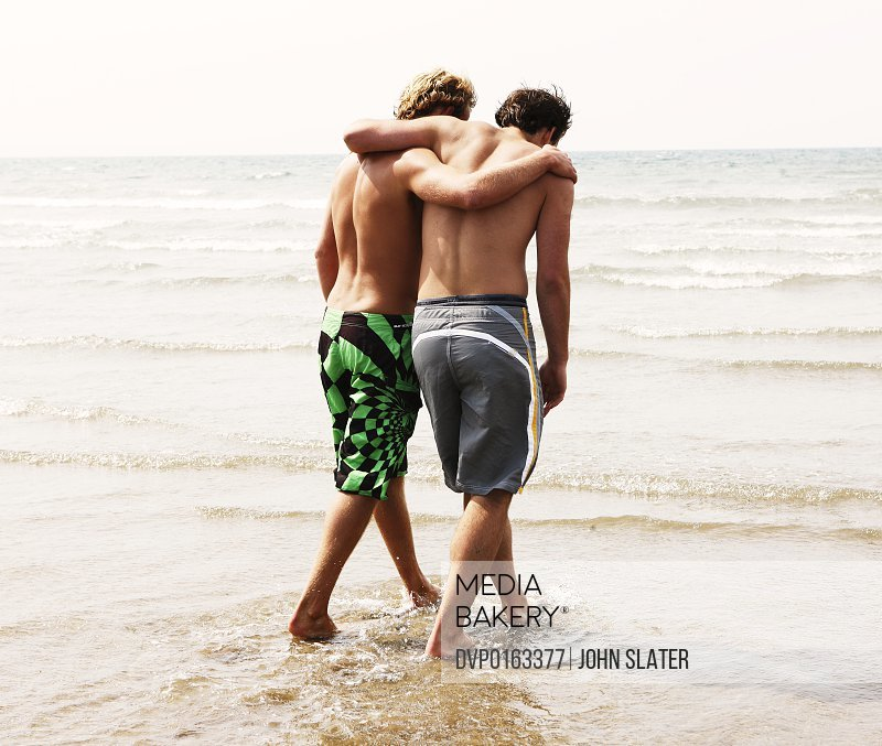 two young men with arms around each other in sea