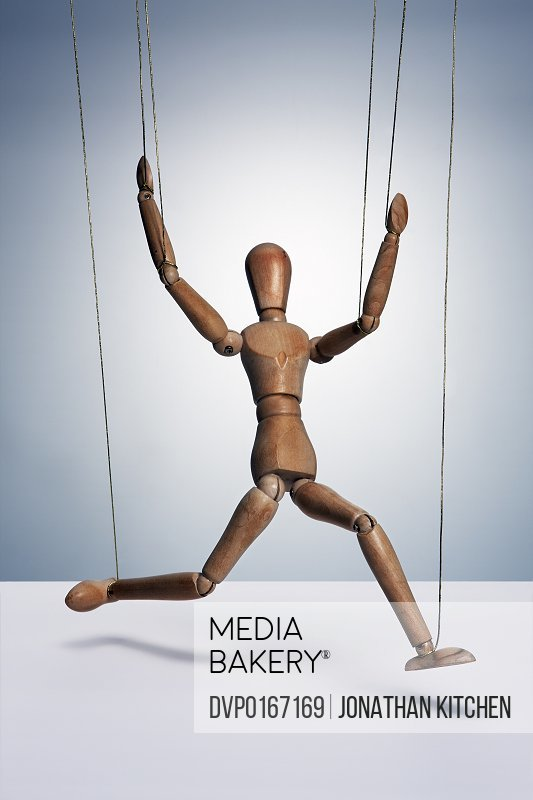 A wooden man controlled by strings