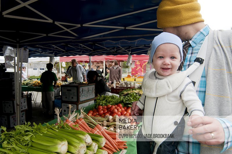 Father and baby browsing produce at organic farmers market
