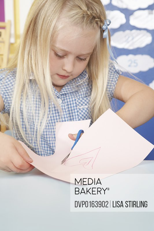 Young school girl cutting out drawing