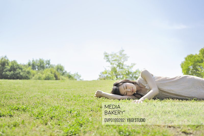 Woman laying down in nature eyes closed