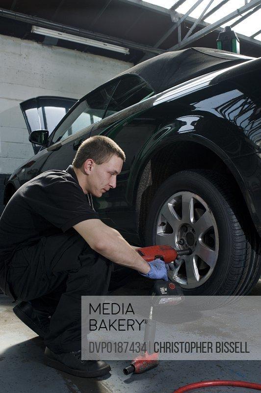 Mechanic putting wheel onto car