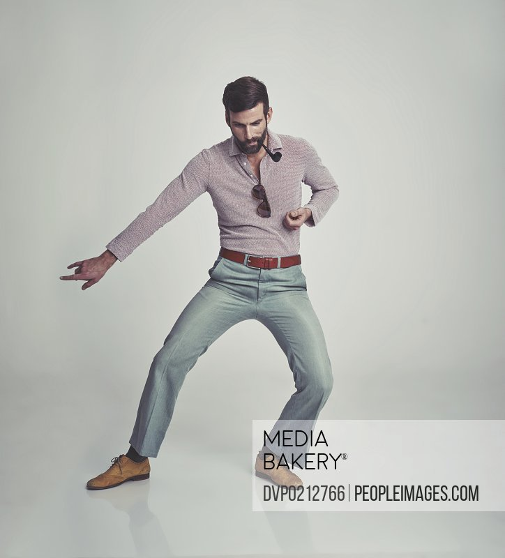 Studio shot of a handsome man doing some dance moves while wearing retro 70s style clothing