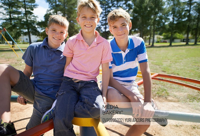 Portrait of three young brothers sitting on a merry go round in a park