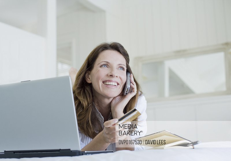 Woman using mobile phone holding credit card