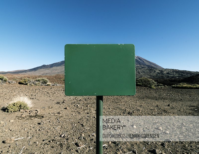 Blank green sign on a pole standing in the middle of bleak desert