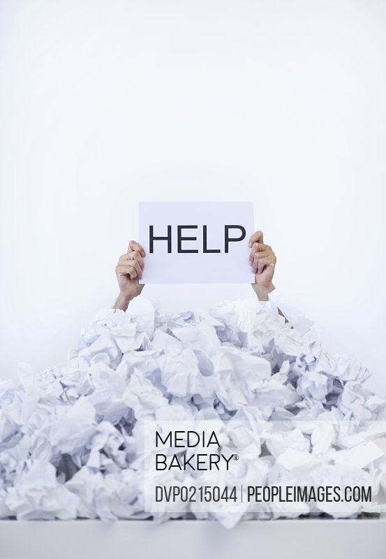 Hands holding up a help placard from below a pile of papers
