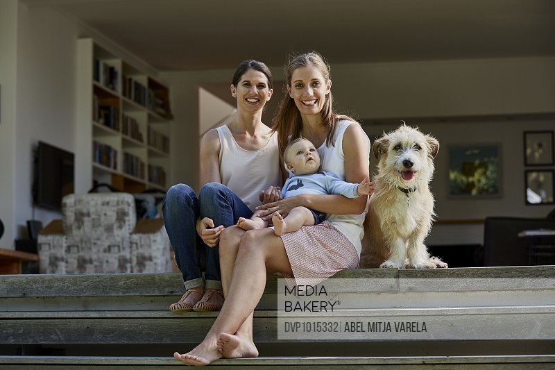 Lesbian couple with baby boy and dog on patio