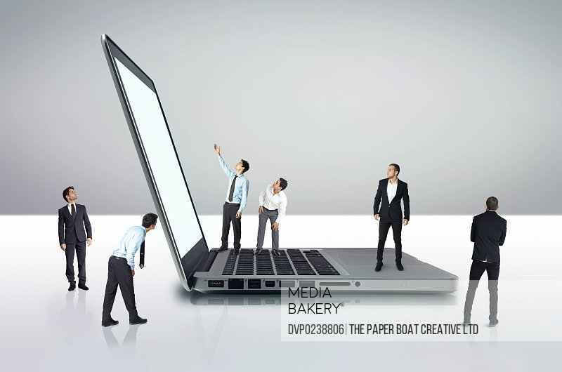 Group of businessmen standing by a giant laptop