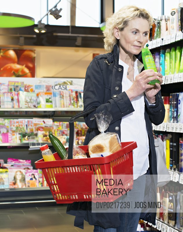 mature woman smelling shampoo insupermarket