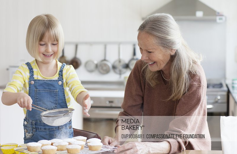 Granddaughter and Grandmother baking cupcakes in kitchen