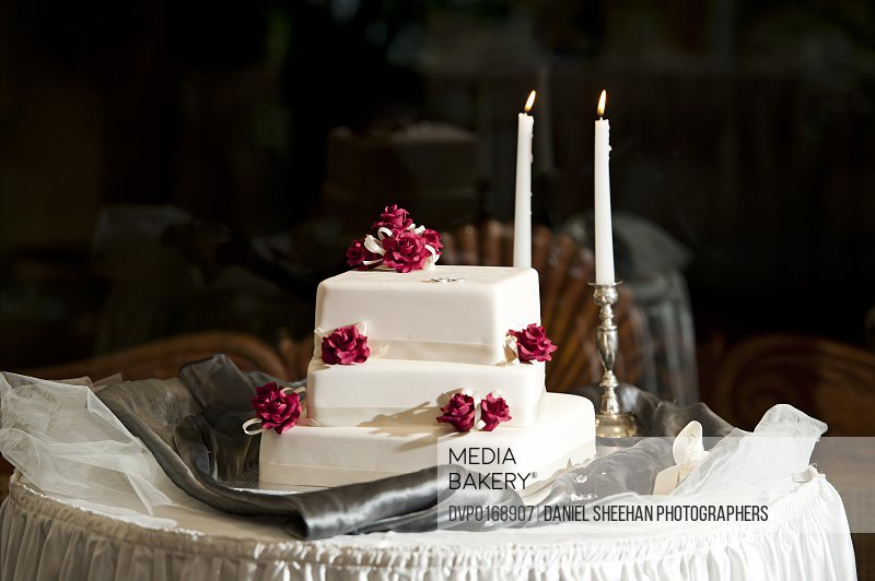 White wedding cake with candles in background