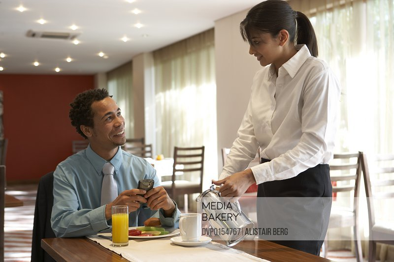 Businessman having breakfast and using a Blackberry style mobile communication device in hotel breakfast room.