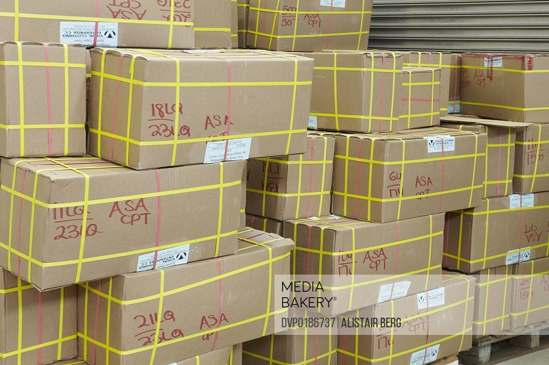 Boxes stacked up awaiting delivery inside a large distribution warehouse