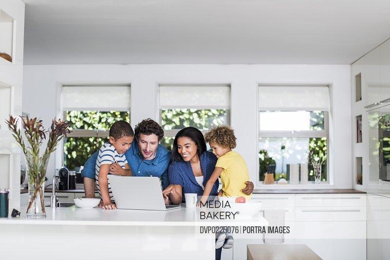 Multi-ethnic family using laptop