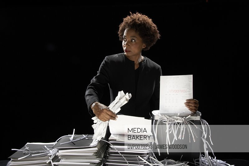 Businesswoman shredding documents looking to one side