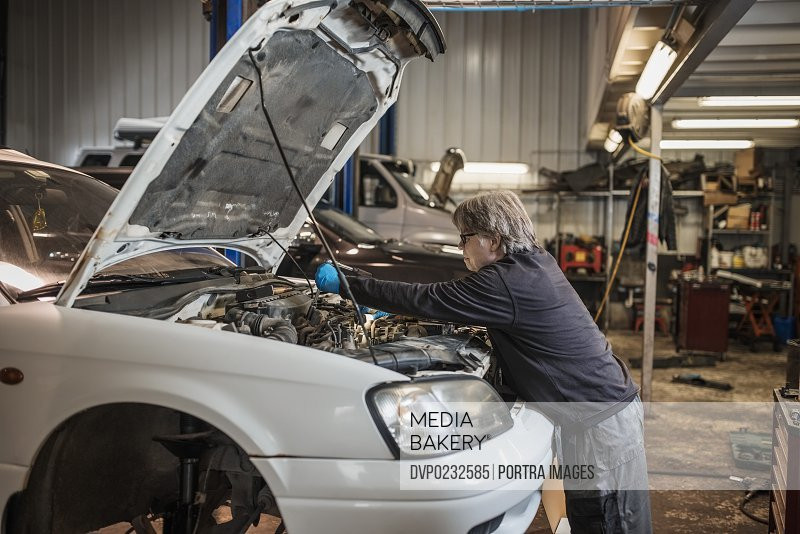 Side view of mechanic working on car engine at workshop
