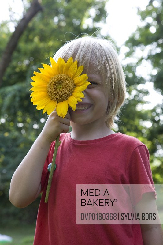 Child Smiling with Flower