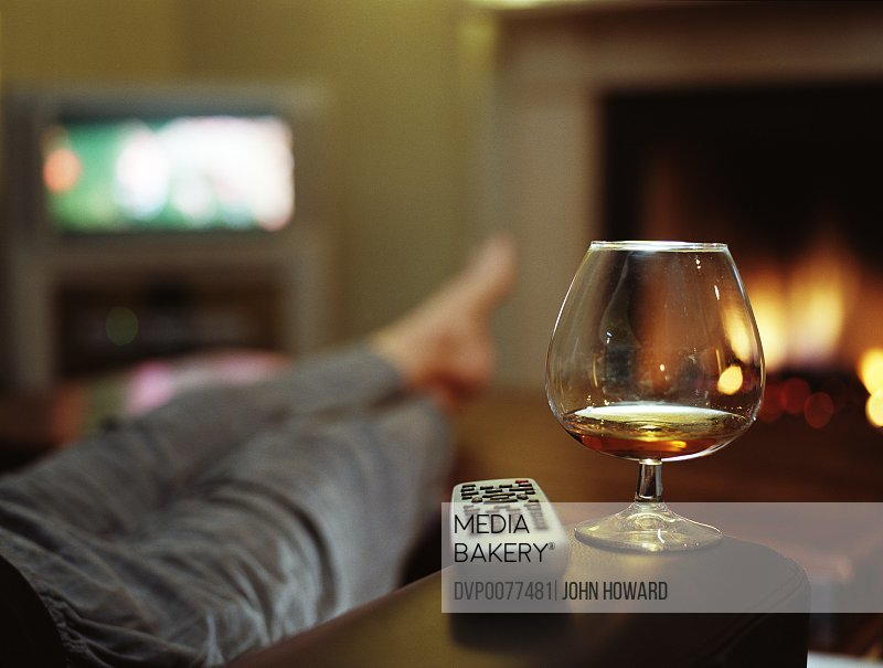 Person in in living room (focus on brandy glass and remote control)