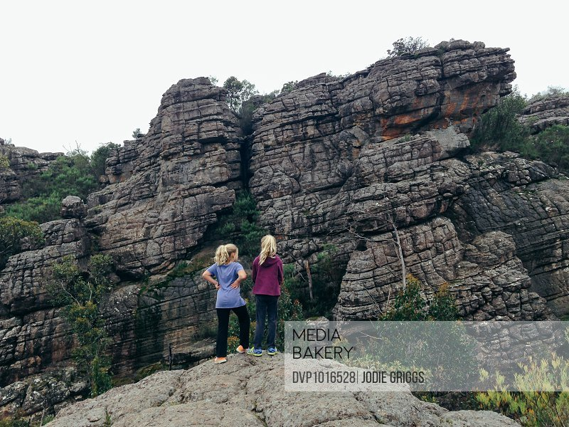 Children standing together on rocky cliff