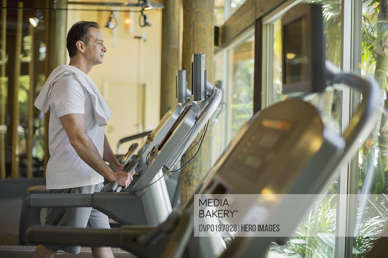 Side view of man exercising on treadmill at health club