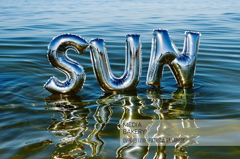 The word 'Sun' reflecting in ocean water