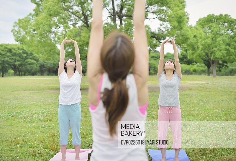 Female yoga instructor teaching yoga in park