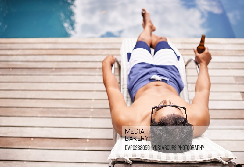 Rear view shot of a young man lounging be the pool with a beer