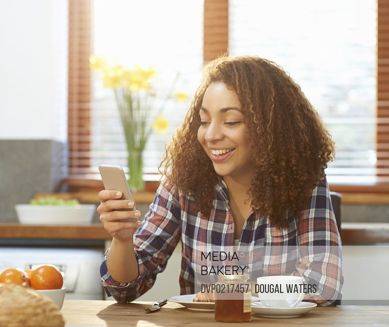 Woman using phone at breakfast table