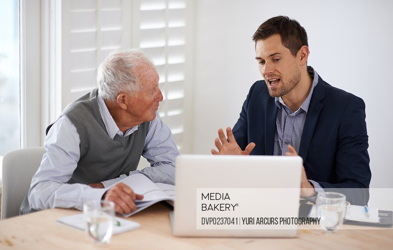 A young businessman explaining information to an elderly man
