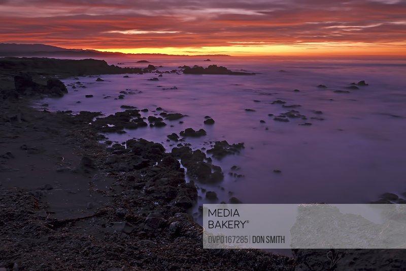 A vivd dawn sky casts its reflective color over the Pacific Ocean near San Simeon Big Sur California USA