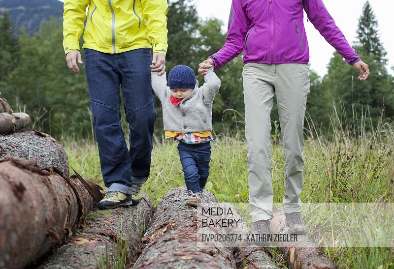 young parents and child balancing on logs