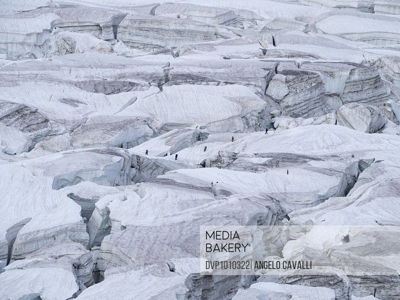 climbers among crevasses in a glacier