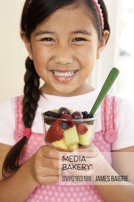 Young girl enjoying healthy fruit cup