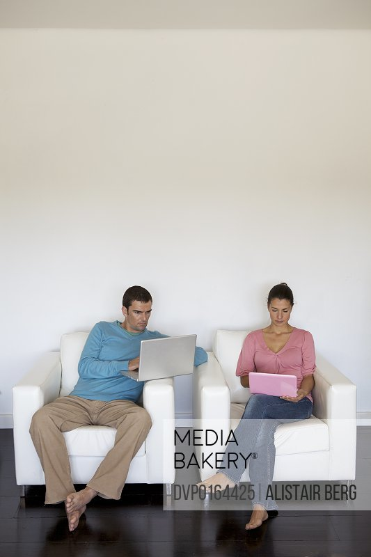 Couple using laptop computers in a modern residential house