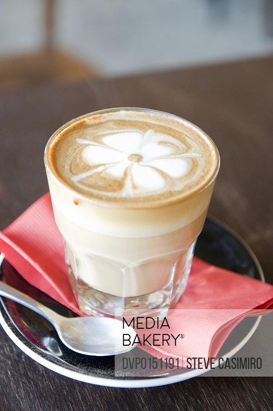 Cafe latte in glass with decorative pattern in foam.