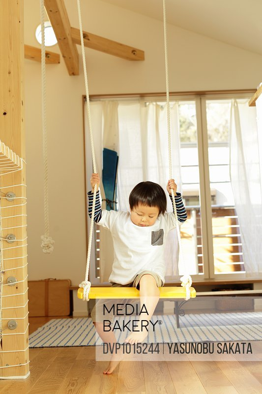 Little boy playing on swing in the room