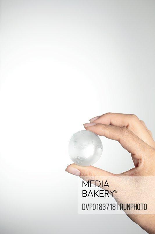 Hand holding a glass globe