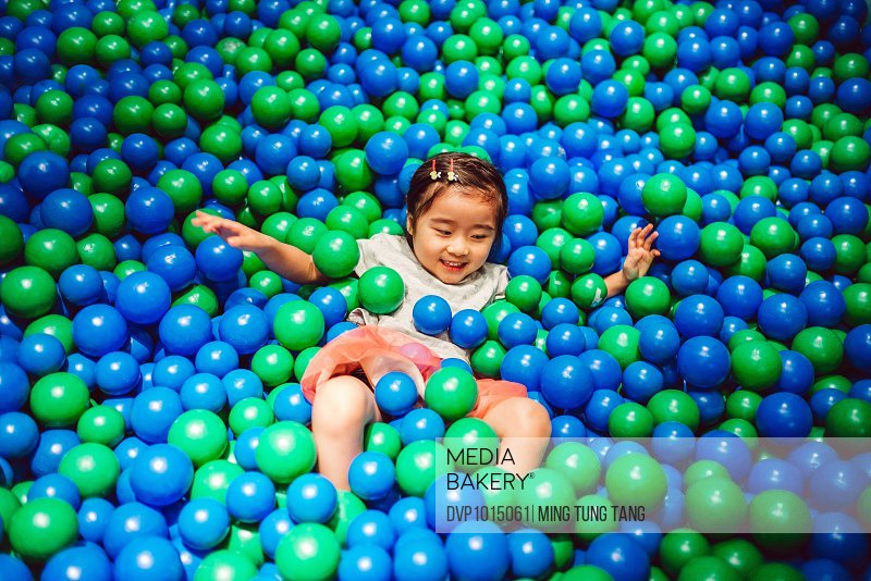 Little girl playing in the ball pit joyfully