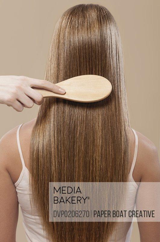 Close up of hair brushing straight brown hair