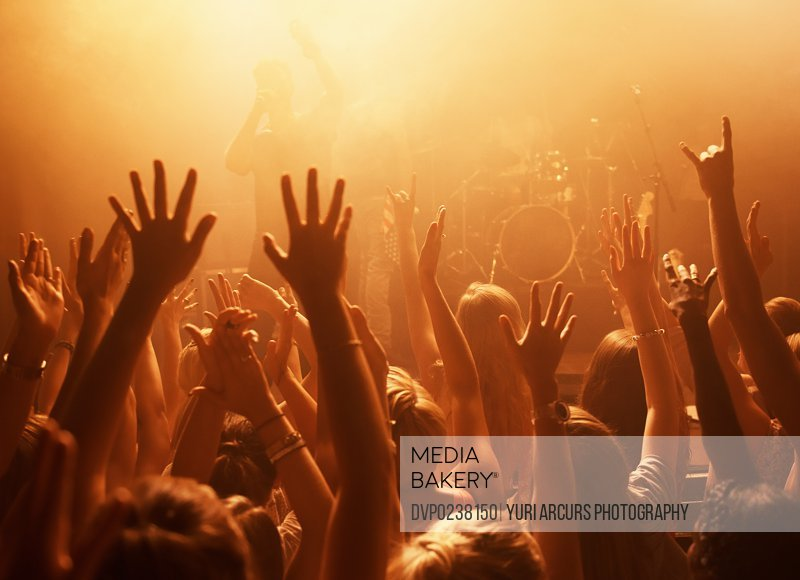 Rearview of a crowd at a music gig with their hands raised in the air. This concert was created for the sole purpose of this photo shoot, featuring 300 models and 3 live bands. All people in this shoot are model released.