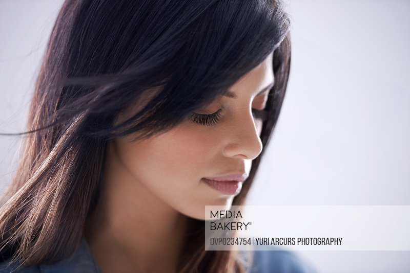 Studio shot of a gorgeous brunette model with her eyes closed