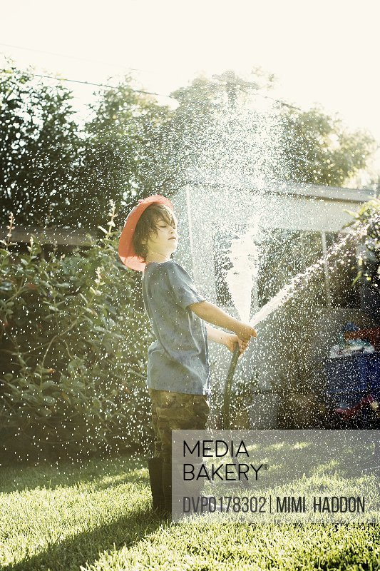 Young Boy Playing With Garden Hose