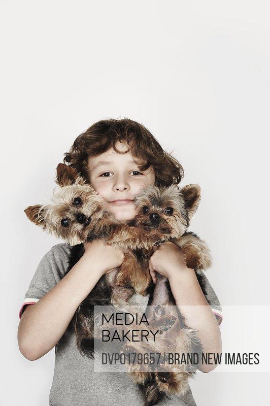 Portrait of boy hugging his pet dogs