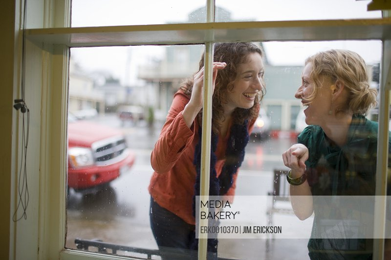 Two curious women looking through the window of a store.