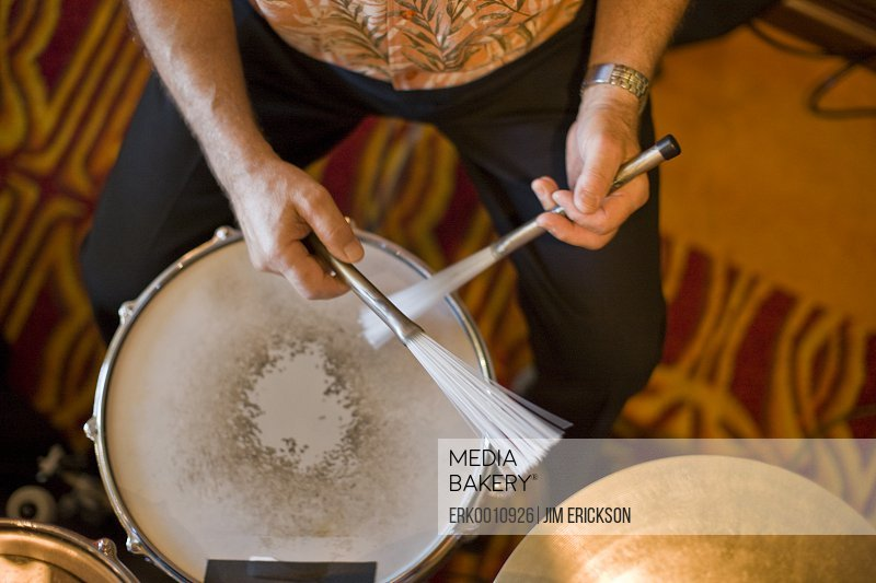 Man playing a drum with feathered drumsticks.