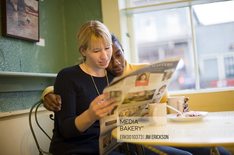 Two women reading a newspaper at a cafe table.
