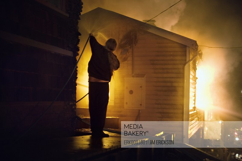 An individual is extinguishing a house on fire.