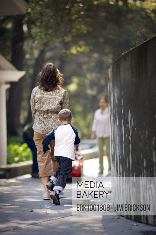 Young boy following his mother on a footpath.